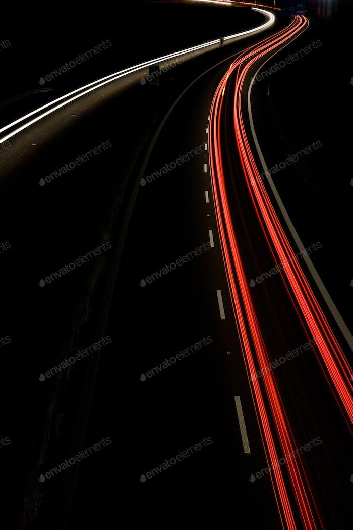 Autos bewegen sich schnell auf einer Nachtautobahn (Bewegung verschwommenes Bild)