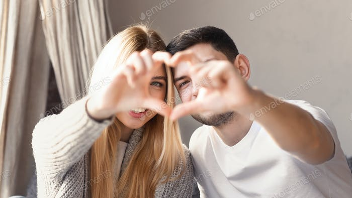 Beautiful couple making heart with their hands at home