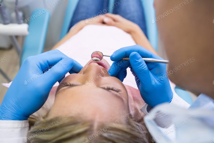 Patient lying on bed while dentist examining at clinic