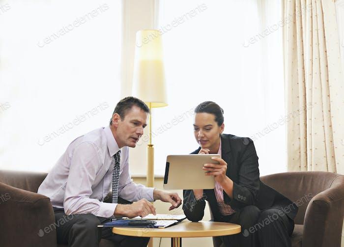 Kaukasische Geschäftsleute mit digitalem Tablet in Lounge