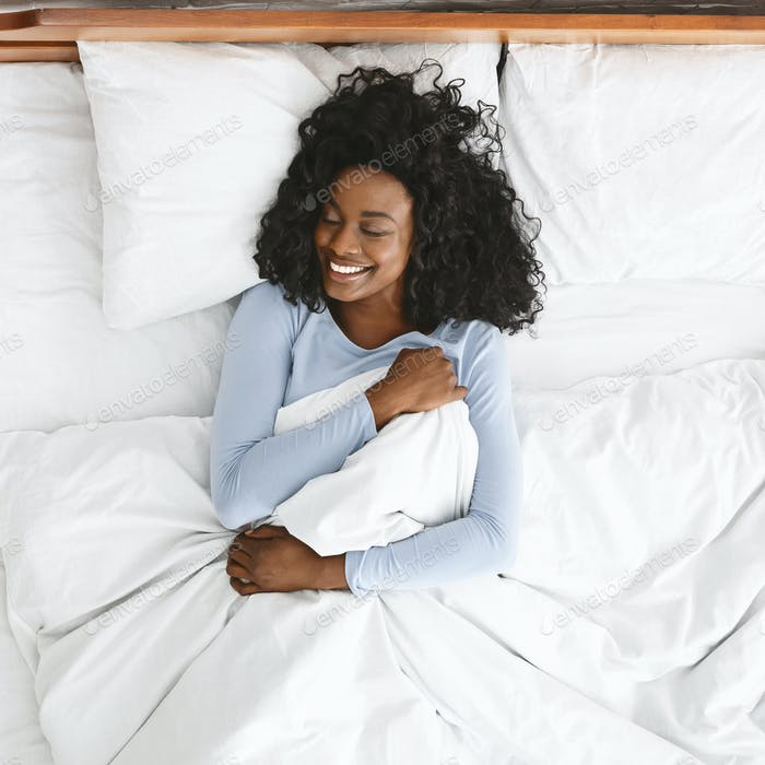 Top view of smiling woman waking up in her bed