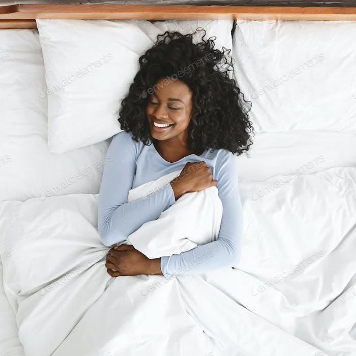 Draufsicht der lächelnden Frau aufwachen in ihrem Bett