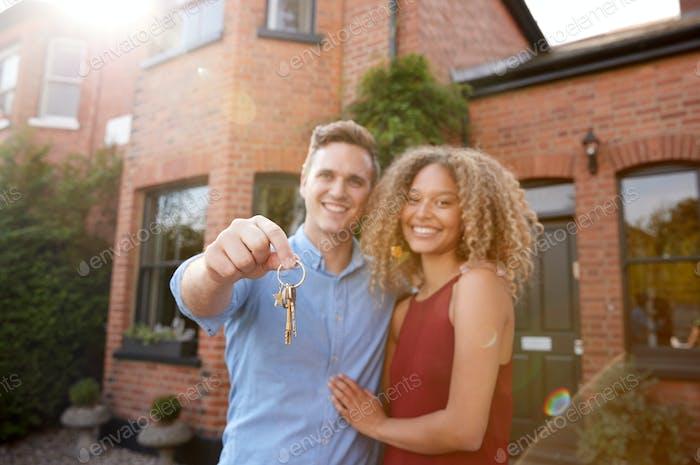 Porträt von aufgeregt junge paar stehend außerhalb neue Hause halten Schlüssel zusammen