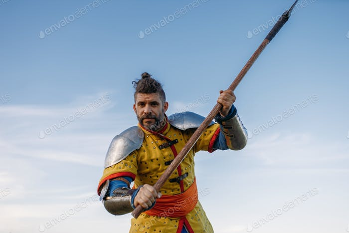 Old medieval knight in armor holds axe