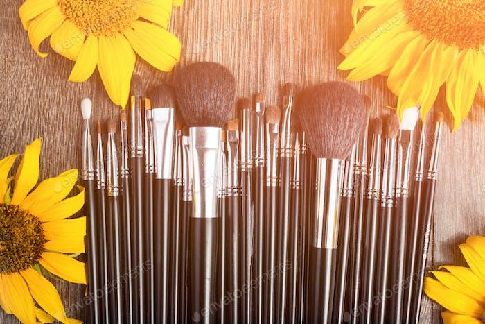 Professional Make up brushes next to beautiful wild flowers