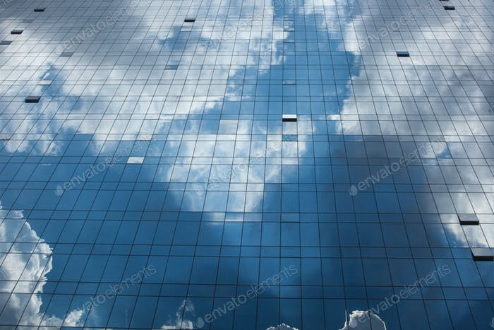 Abstract glass building reflecting clouds and blue sky