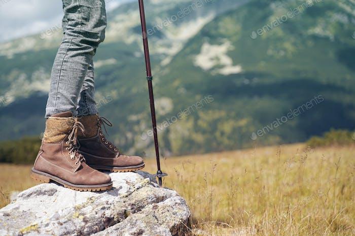 Frau mit Lederstiefel und Wanderstock am Berg