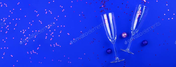 Champagne glasses with confetti on classic blue