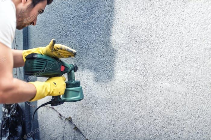 Человек рисует серую стену, ремонт наружных стен нового дома