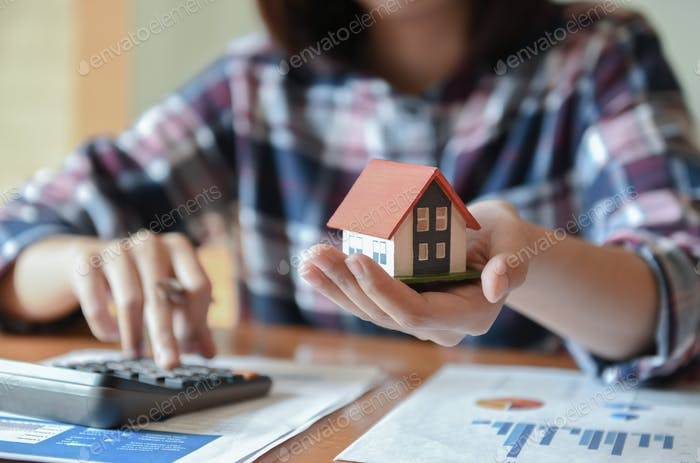 Home salesman holding a model house in hand.