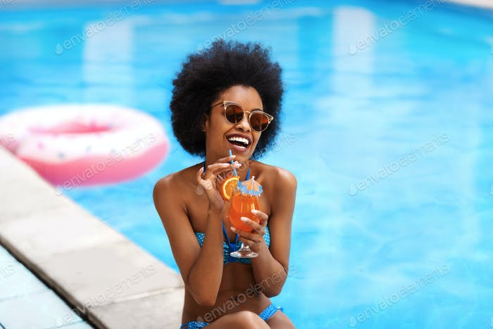 Pretty black lady drinking tropical beach cocktail and laughing by outdoor pool