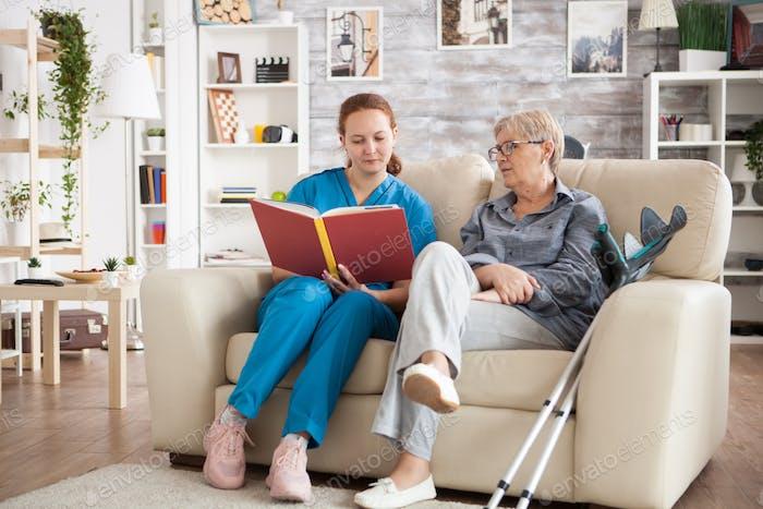 Junge Krankenschwester sitzt auf Couch im Pflegeheim