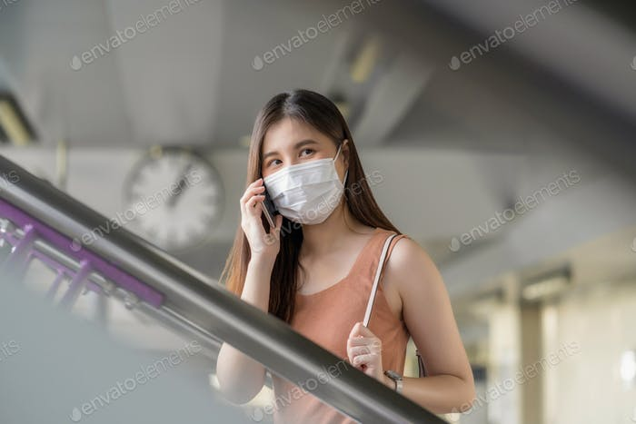 Young Asian woman passenger wearing surgical mask and using mobile phone