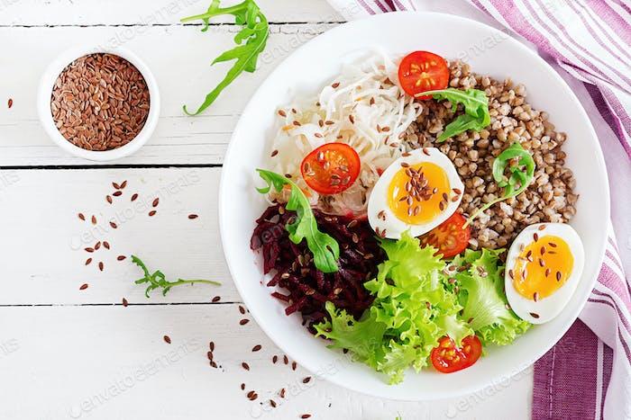 Buckwheat porridge buddha bowls with beetroot, cabbage, boiled eggs and  fresh tomato
