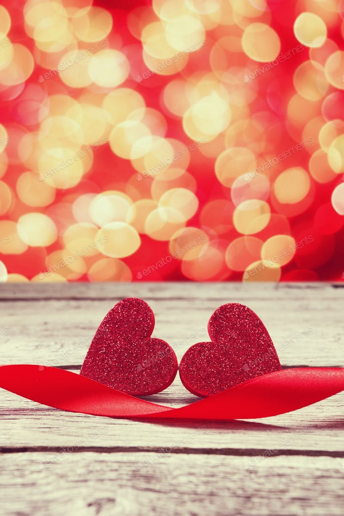 Bokeh background, handmade hearts and ribbon on wood