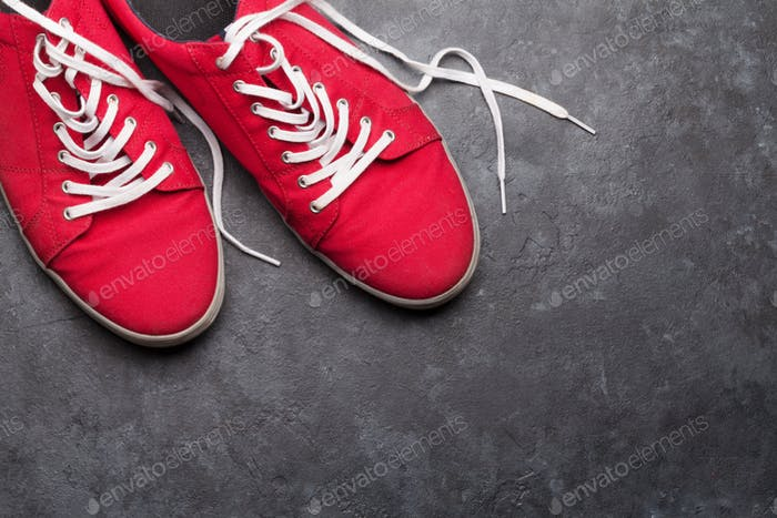 Pair of red sneakers over stone