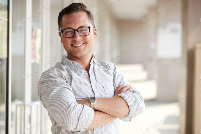 Portrait Of Smiling Male School Teacher Standing In Corridor Of College Building