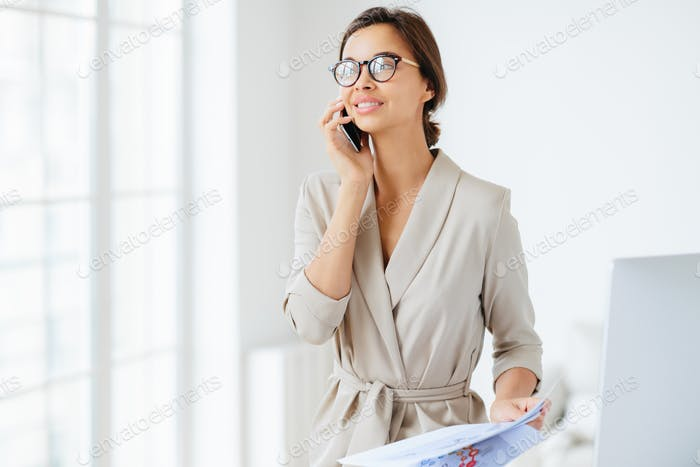 Happy thoughtful successful female employee has telephone conversation