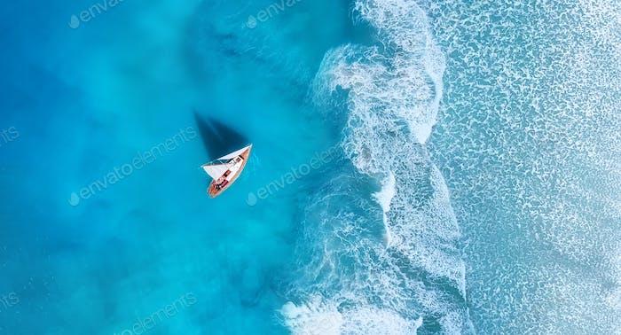 Welle und Boot am Strand als Hintergrund. Strand und Wellen aus der Draufsicht.
