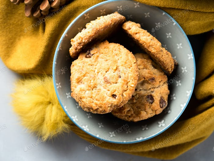 Mug of tea with milk and cookies in a soft winter scarf