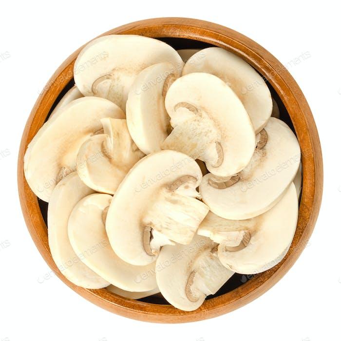 Sliced white champignon mushrooms in wooden bowl
