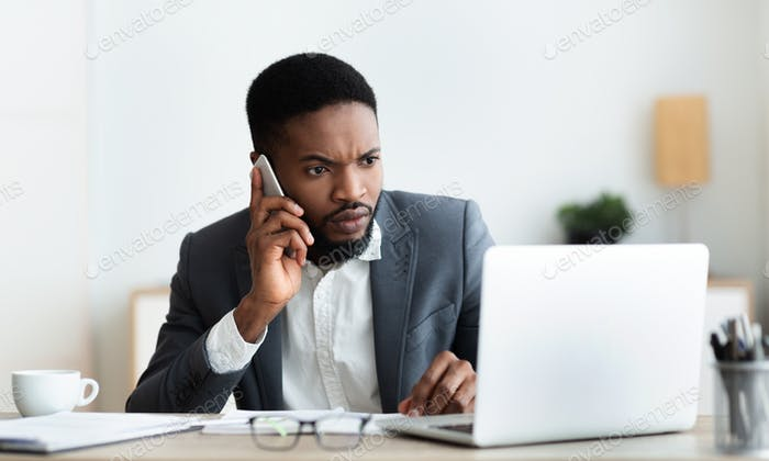 Concerned businessman talking on cellphone and looking at laptop screen
