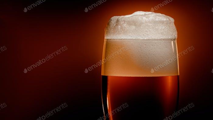 Lagerbier setzt sich im Glas mit einer weißen Schaumkappe ab