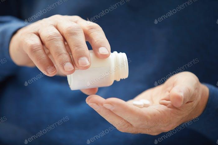 Senior Man Taking Vitamins Closeup