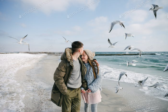 Young Happy Couple Hugging on Winter Sea Shore With Seagulls