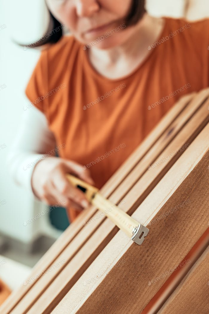 Female carpenter tape measuring wooden crate