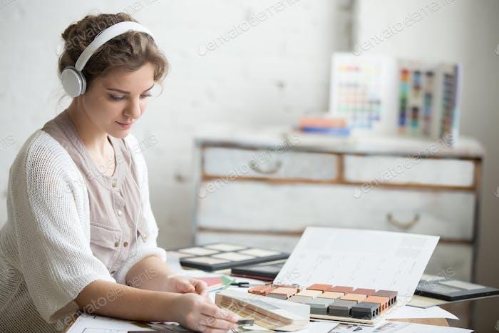 Junge Frau in Kopfhörer bei der Arbeit