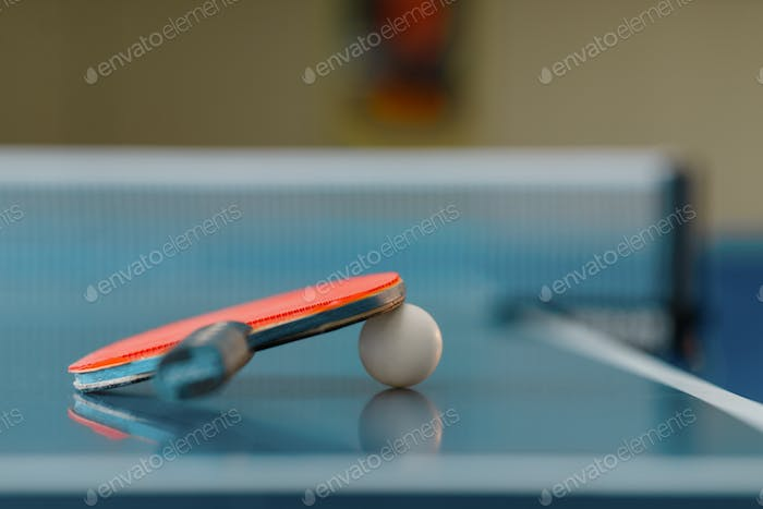 Ping pong racket and ball on game table, closeup