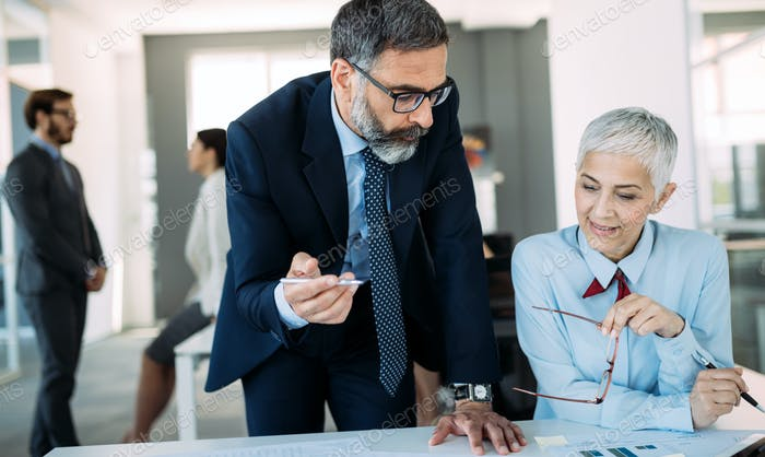 Happy mature businessman and businesswoman planning in office