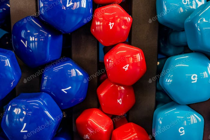Stand with colorful dumbbells in modern gym