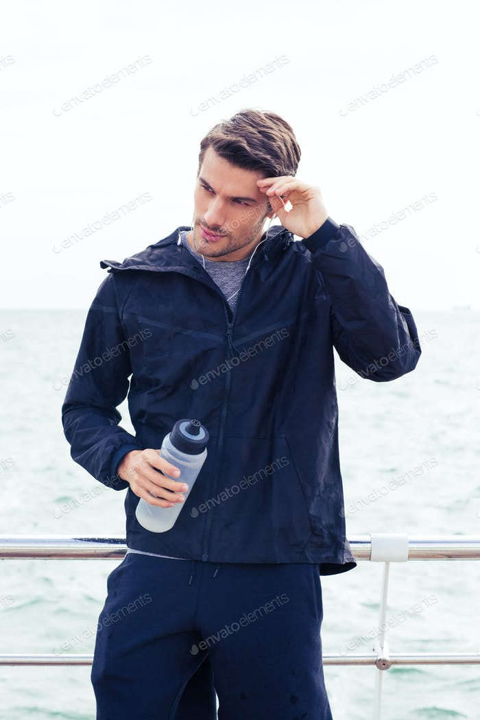 Man standing with bottle of water outdoors