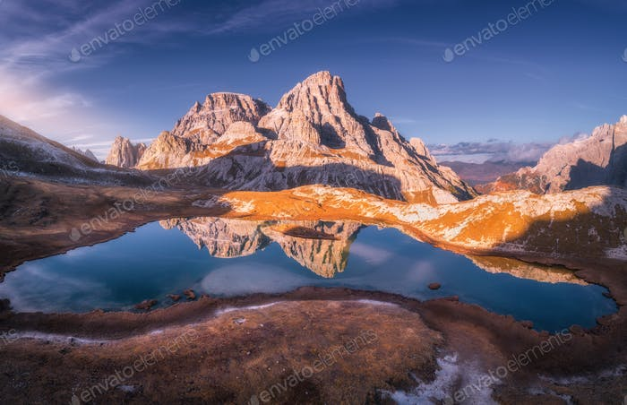 Aerial view of mountain lake with reflection at sunset in autumn