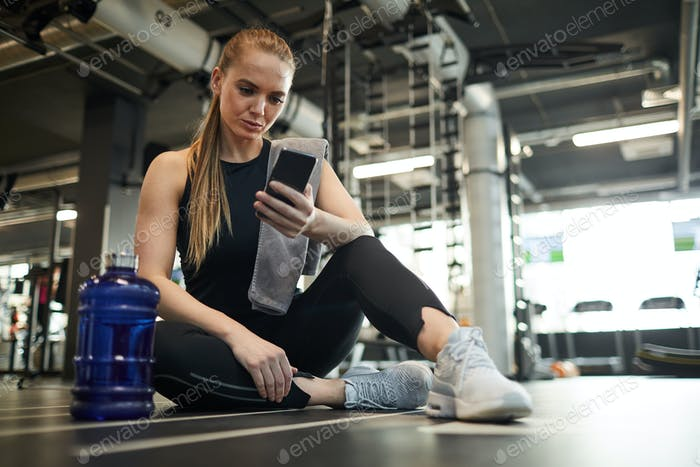 Young Woman Taking Break in Gym