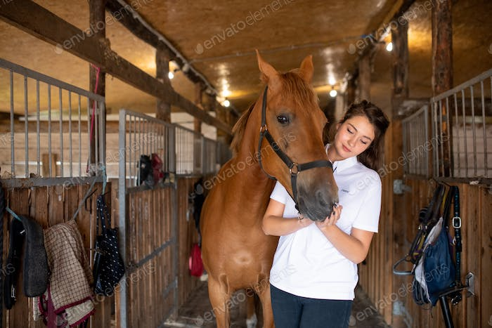 Young active woman in white shirt standing inside stable by purebred racehorse