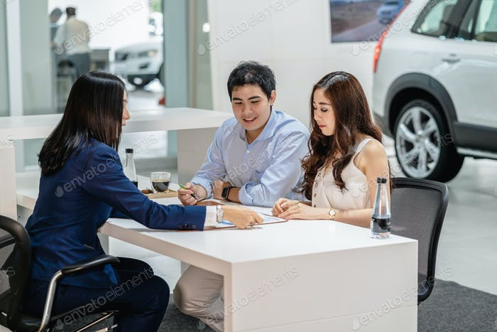 Asian Saleswoman explaining sales contract to couple customer before decision