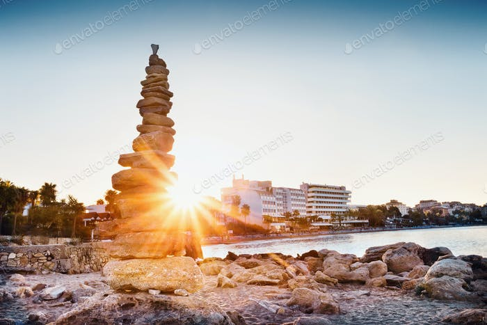 Cairn on seashore shot in front of sun