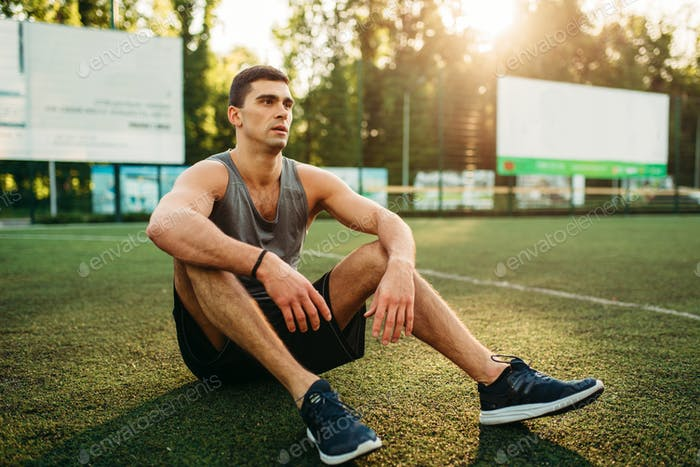Athlete holds bottle of water, outdoor workout
