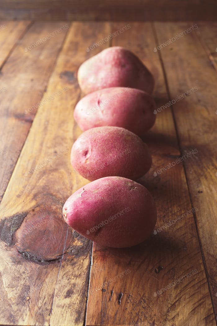 group of red potatoes uncooked on wooden rustic table