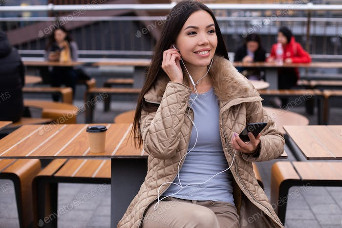 Young cheerful casual woman in down jacket happily listening music in earphones on cellphone outdoor