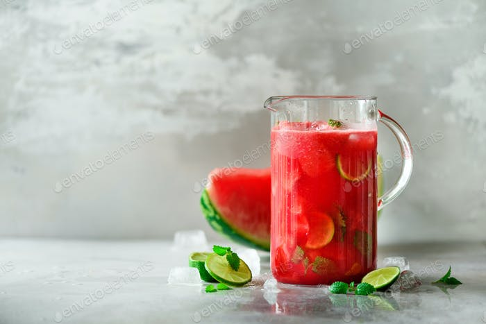 Detox water with watermelon, lime, mint and ice on light background, copy space