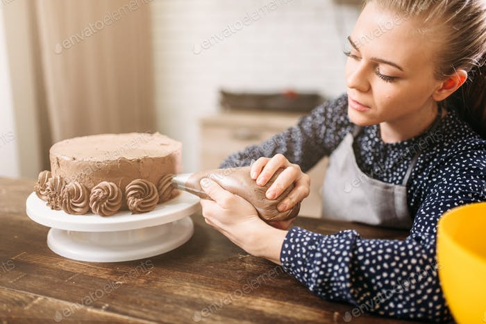 Woman decorate cake with culinary syringe