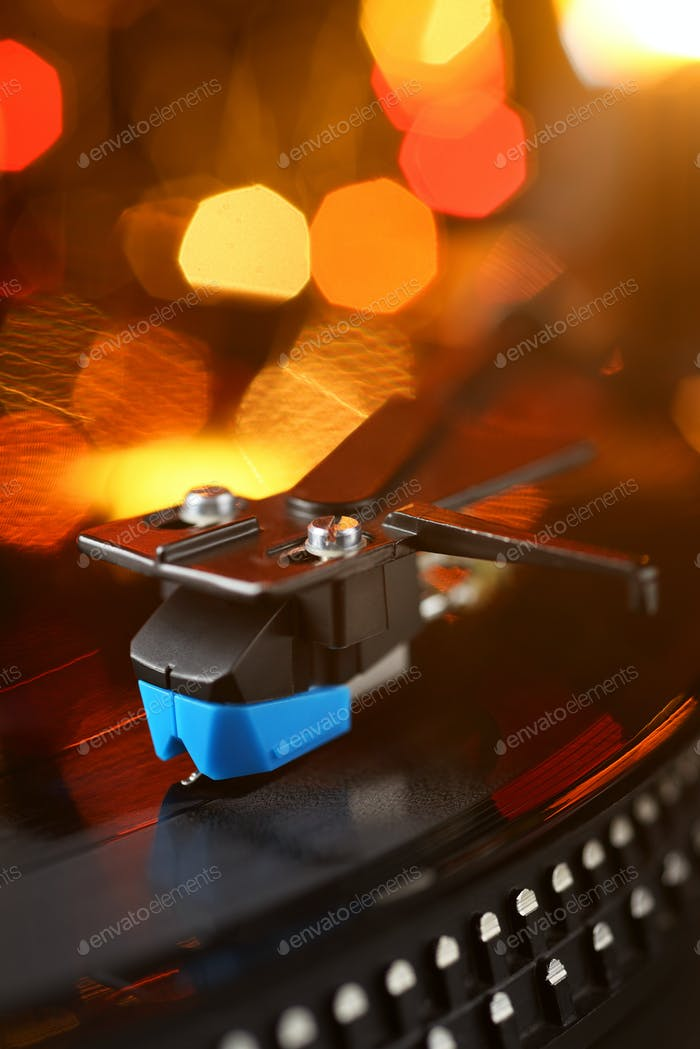 Vinyl player tonearm with LP record and blured lights.