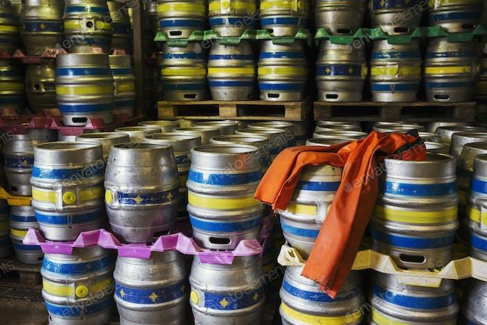 Stacks of metal beer kegs in a brewery.