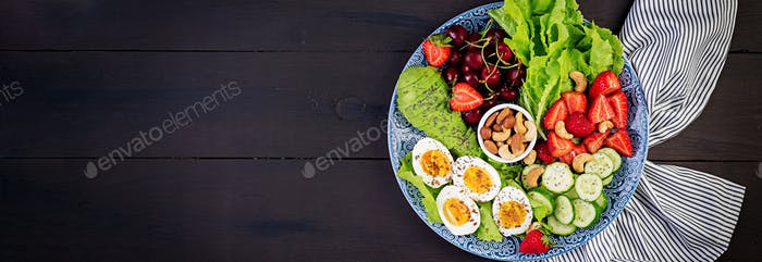 Plate with a paleo diet food. Boiled eggs, avocado, cucumber, nu
