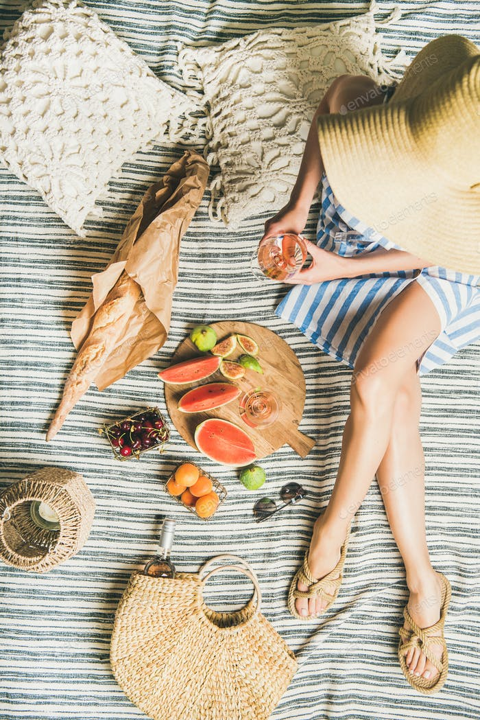 Picnic concept with woman in dress, wine, fruits and baguette