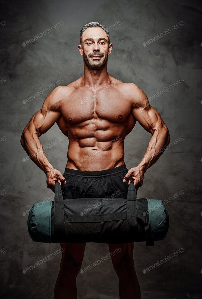 Athletic man isolated on a white background doing and exercise with a weight bag